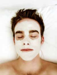man with eyes closed, relaxing with herbal face mask.
